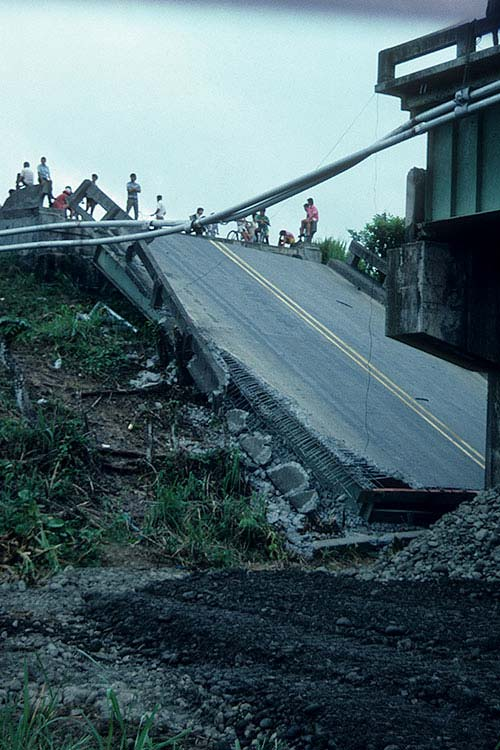 Costa Rica 1991 – We were traveling from San Jose to Puerto Limon.  As we approached the river, the soil was much worse and the road conditions deteriorated.  The portions of the bridge across the river had collapsed, all due to soil subsidence and lateral spreading undermining the foundations.  This view shows where one abutment had shifted laterally and pulled the other end of the span off of its supports. We had to drive through the river in our truck to get to the other side.
