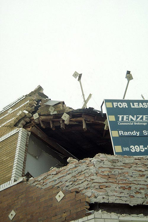 Northridge 1994 - This type of damage was common in many of the unreinforced masonry bearing walls buildings.  Note the retrofit anchors visible in this view, without them the damage probably would have been worse.